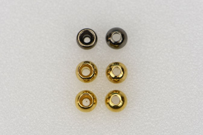 These three pairs of beads show the larger hole (left) drilled into the backside of the beads during the manufacturing process. Always place the bead on the hook by running the hook point through the small hole in the bead.